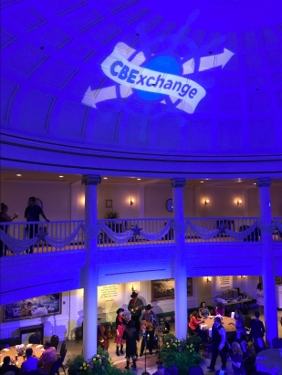 Large room with lighting changd to blue and the CBEExchange logo projected onto the ceiling.