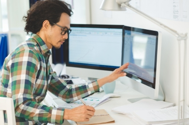 a man sits working independently at a computer