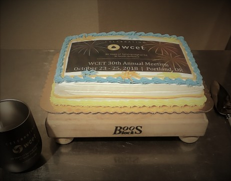 """A small cake with the annual meeting logo printed on top which reads """"celebrating wcetL 30 years of serving higher ed in north america. WCET annual meeting. October 23-25, 2018, Portland, OR"""""""