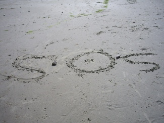 Photo of a beach with the letters SOS spelled out in the sand.