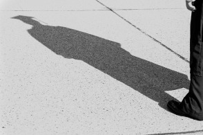Picture of a college graduate looking into his shadow on the sidewalk.