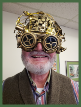 Mike wearing bronze and gold steampunk glasses with gears, wires, and gold lenses.