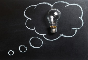Picture of a single light bulb placed against a blackboard. The light bulb is surrounded by a white cloud drawn in chalk.