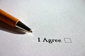"""Picture of a sheet of white paper that reads, """"I agree"""" which a blank box to check to the right."""