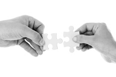 Picture of two hands, each holding a piece of the puzzle that fits perfectly with the other.