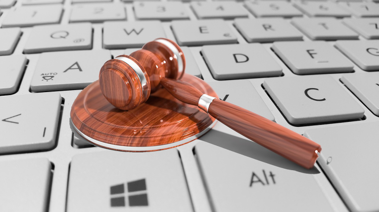 A photo of a gavel on a keyboard representing a legal finding in a technology-based case.