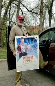 Mike standing outside his carholding a Buckaroo Banzai movie poster