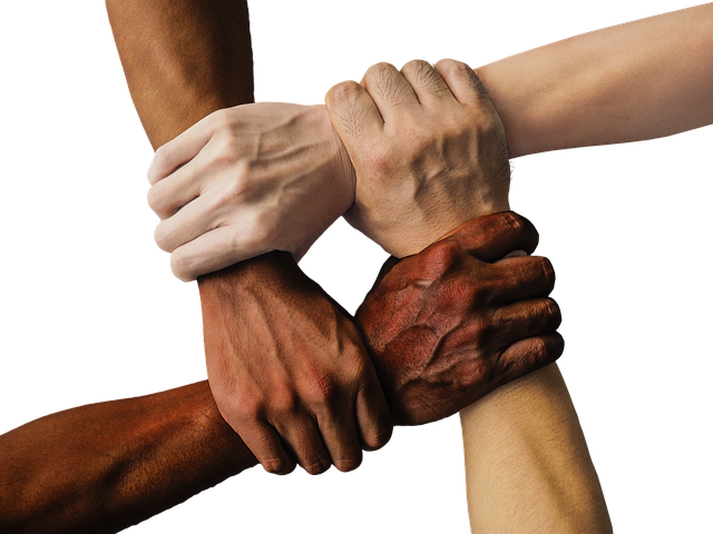 Picture of four hands connected. Each hand is clasping a wrist.