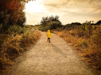 A child in a yellow raincoat runs down a road