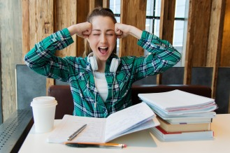 A young woman holds her head with her hands and screams. she is surrounded by notebooks as if studying.