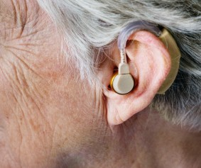 Photograph of the side of a person's head and a hearing aid attached to their ear.