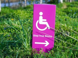 "Photograph showing a pink accessibility sign, which points towards a ""Step Free Route."""