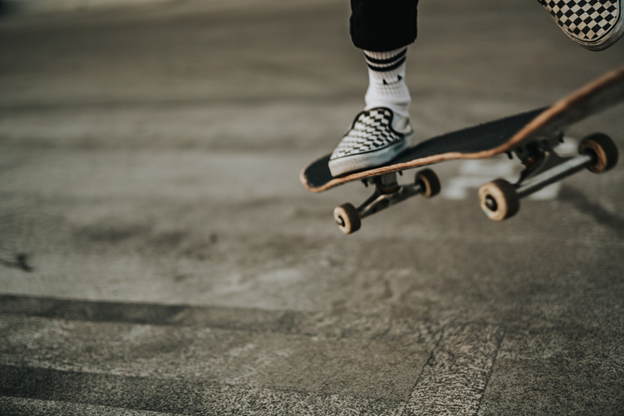 A person on a skate board jumping over sidewalk