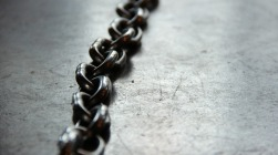 a dark metal chain on a concrete floor