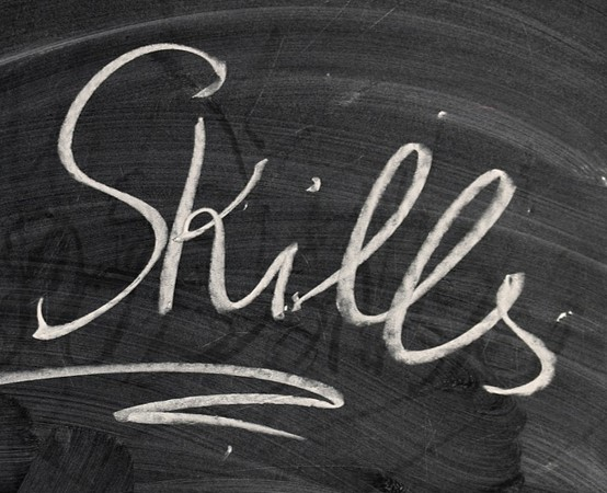 "The word ""skills"" written on a black chalkboard in white chalk."