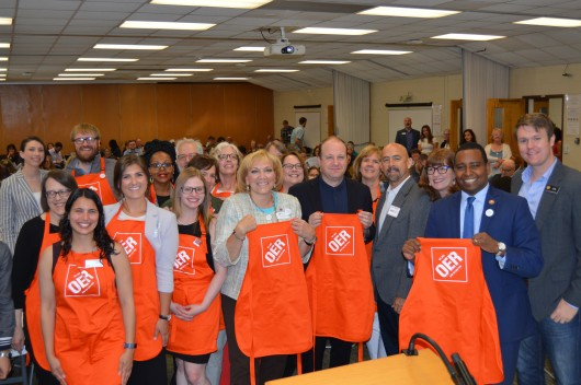 "Attendees at a conference pose for a photo holding aprons that read ""OER"""