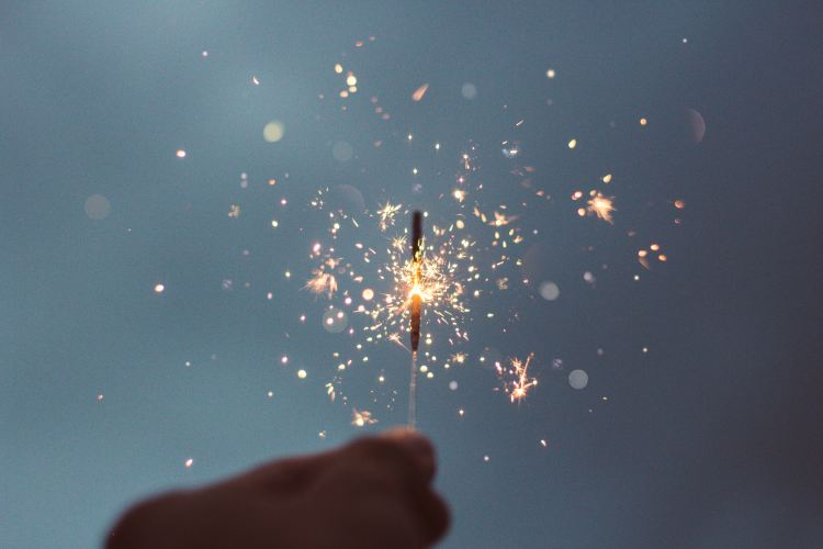 a person holding a lit sparkler