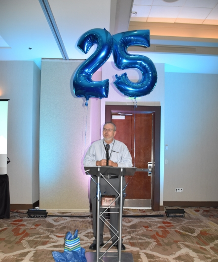 Russ Poulin addressing room with large balloons that say 25