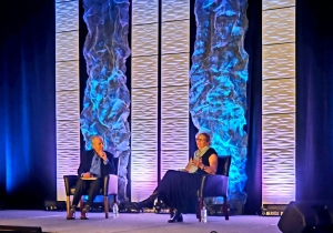 Diane Auer Jones and Michael Goldstien sit on stage during a session