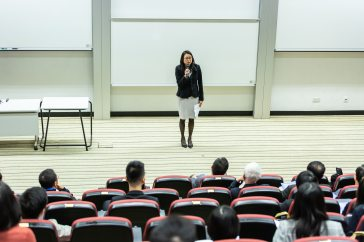 A woman lecturing to a large class