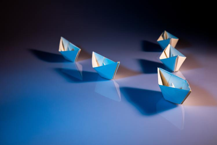 small paper boats in a triagle shape with one boat leading the others