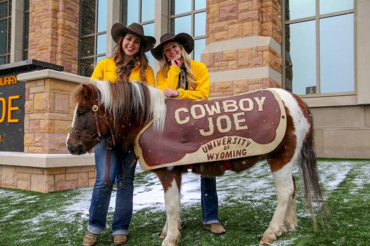 A pony with a cover that says Cowboy Joe University of Wyoming, posing with two women in cowboy hats