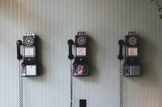 three rotary phones on a wall