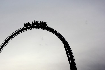 A roller coaster cart filled with people about to go over a long drop