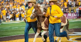 Two women in cowboy hats run with Cowboy Joe, the pony, on a football field