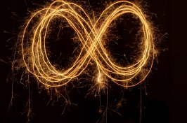 an infinity sympol drawn using sparklers/light