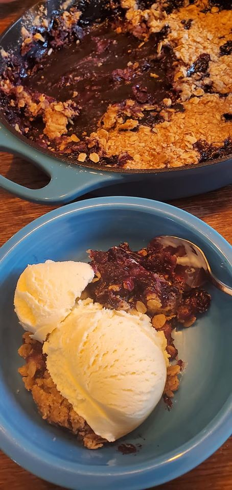 photo of a castiron pan with blueberry cobbler and ice cream