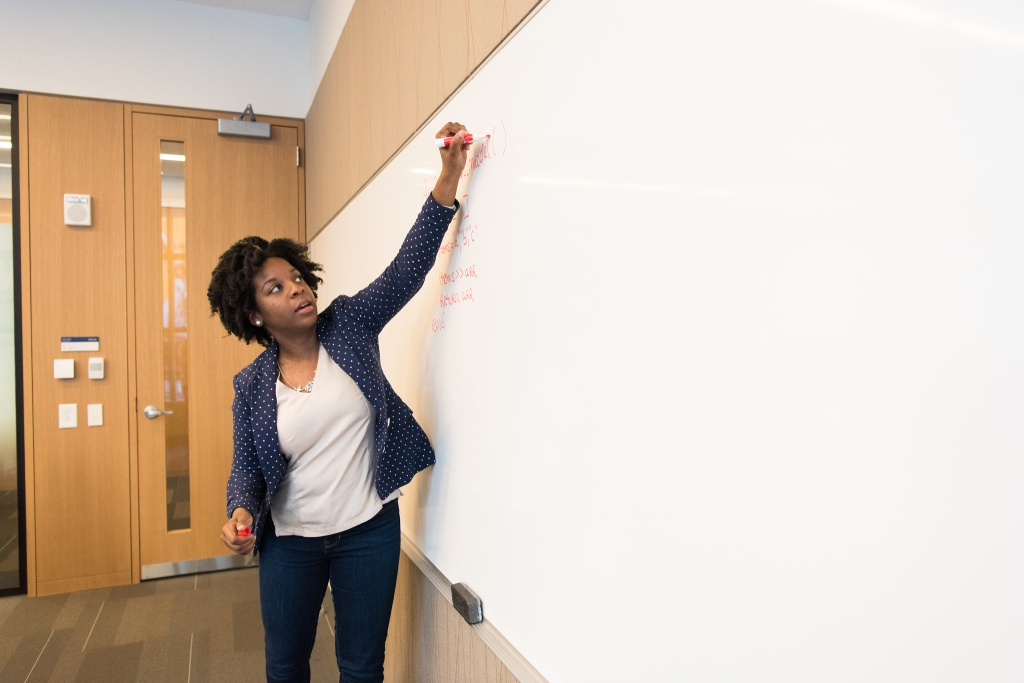 a professor writing on a board